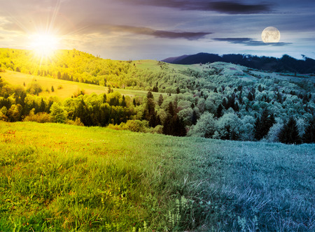 time change above mountainous countryside in springtime. grassy meadows and forested hill. freshness of nature concept Stock Photo