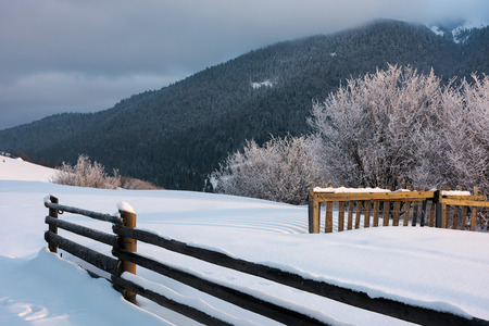 wooden fence on snowy hill in morning light. trees in glittering hoarfrost at the edge of a slope. forested mountain ridge in the distance touches low hanging clouds. magical moments of winter season Stock Photo - 113389566