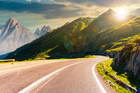 road in mountains with rocky ridge in the distance at sunset. composite image. travel by car concept Stock Photo - 113389569