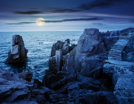 stone steps on rocky cliffs above the sea. gorgeous cloudscape at night in full moon light