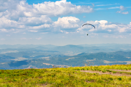 Skydiving training in mountains,  flying above the distant hills. parachute extreme sport.   absolute freedom concept. wonderful summer weather Stock Photo - 113389627