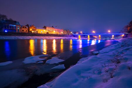Uzhgorod, Ukraine - DEC 26, 2016: beautiful evening cityscape of old european town Uzhgorod in winter. wonderful cloudy sky over the river Uzh with some ice and snow on the shore. citylights reflect on the water surface Editorial