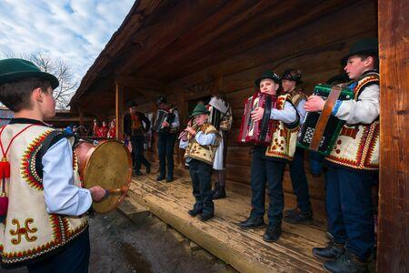 Uzhgorod, Ukraine - Jan 13, 2018: Vasylya festival celebrating in Museum of Folk Architecture and Life. Group of kids in traditional suits singing hutsul carols
