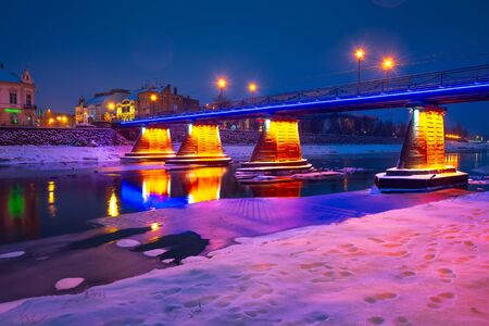 Uzhgorod, Ukraine - DEC 26, 2016: pedestrian bridge through the river Uzh at night. beautiful cityscape of old european town Uzhgorod in winter Editorial