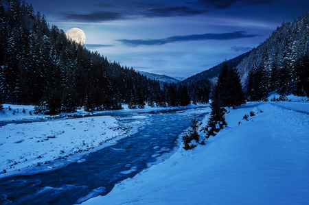 mountain river in winter at night in full moon light. snow covered river banks. forest in snow on the distant mountain. cloudy morning