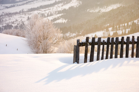 wooden fence in snow and morning sunlight. beautiful winter countryside background Stock Photo - 113582495