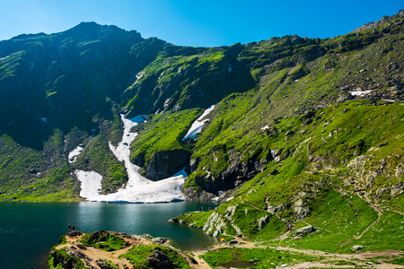 Lake Balea of Fagaras mountains. last pieces of snow on the grassy hills. beauty of Romania 스톡 콘텐츠