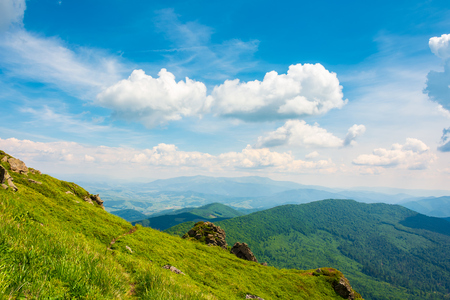 rock on grassy slope of a mountain. beautiful view from the top of a hill. wonderful summer landscape on a sunny day. beautiful clouds on a blue sky Stock Photo - 113582520