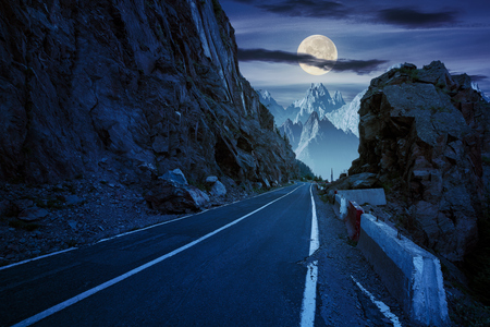 road in to the high mountains between rocky cliff at night in full moon light. composite image of dangerous path to the dreams.  Stock Photo