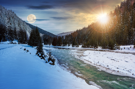 day and night time change concept. mountain river in winter with sun and moon. snow covered river banks. forest in snow on the distant mountain. cloudy morning Stock Photo
