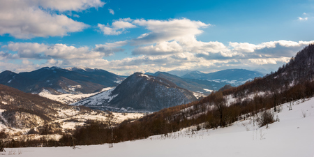panorama of winter countryside in mountains. wonderful sunny day with gorgeous cloudscape. dark forest on the snow covered hills. village down in the distant valley. faraway ridge with snowy tops Stock Photo