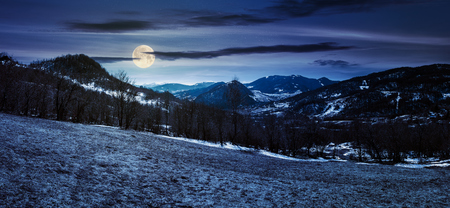 panorama of mountainous countryside in springtime at night in full moon light. leafless trees and weathered grass on a meadow. spots of snow on the forested hills. gorgeous blue sky with some cirrus clouds