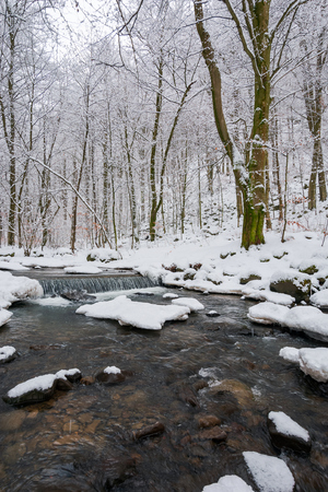 small cascade on the forest creek in winter. beautiful nature scenery Stock Photo