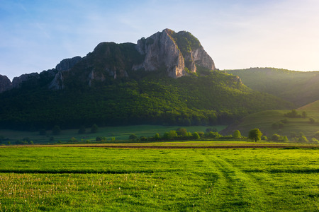 beautiful sunrise in mountains. wonderful springtime scenery with trees on a grassy meadow and huge rocky formation in the distance. location Piatra Secuiului, Romania Stock Photo