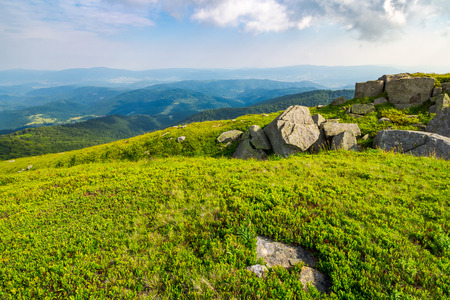 grassy slope with huge rocks. wonderful summer landscape in mountains. grassy slope with huge rocks. wonderful summer landscape in mountains Stock Photo