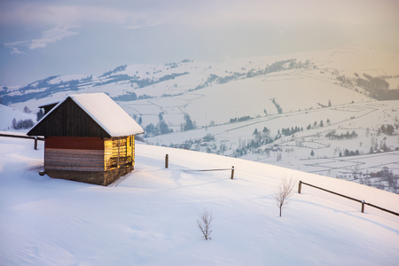 outskirts of the village on the hill. woodshed behind the wooden fence on a snowy slope. peaks of the distant mountain ridge in clouds. wonderful winter tale in gorgeous light Stock Photo - 113787520