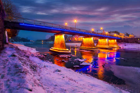 pedestrian bridge through the river Uzh at night. beautiful cityscape of old european town Uzhgorod in winter Stock Photo