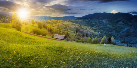 time change above the rural field with dandelions in mountains. beautiful springtime landscape with sun and moon. village in the distance valley. Stock Photo