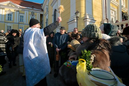 Uzhgorod, Ukraine - JAN 19, 2019: greek catholic epiphany ceremony in cathedral. priest sanctifies people around
