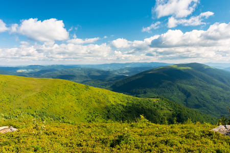 beautiful landscape of carpathian mountains. grassy alpine meadows, deep valleys and distant forested hills. wonderful sunny weather at sunset in summertime. fluffy clouds on the blue sky Stock Photo