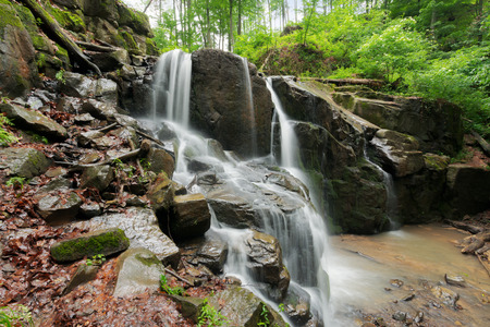 beautiful waterfall among the huge rocks in forest. beautiful nature summer scenery. refreshing environment Stock Photo - 115869371