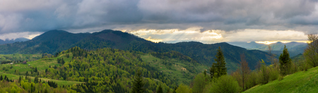 beautiful panorama of mountainous countryside. wonderful springtime landscape. forested rolling hills. overcast sky with sun rays in the distance Stock Photo