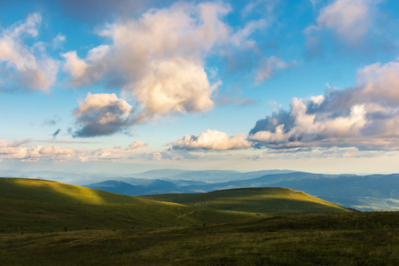 wonderful evening landscape. beautiful view from the grassy hill in to the distant valley and mountain ridge. fluffy clouds on the sky. peaceful idyllic scenery Stock Photo