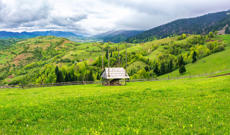 hay shed on a grassy field in mountains. beautiful countryside landscape in springtime. cloudy forenoon. village on the distant hills Stock Photo