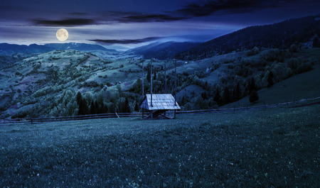 hay shed on a grassy field in mountains. beautiful countryside landscape in springtime at night in full moon light. village on the distant hills Stock Photo