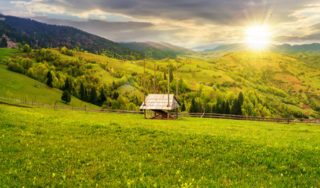 hay shed on a grassy field in mountains. beautiful countryside landscape in springtime at sunset in evening light. cloudy afternoon. village on the distant hills Stock Photo - 115869450