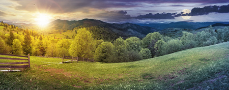day and night time change above panorama of mountainous countryside in springtime. beautiful highland landscape with sun and moon. wooden fence on the grassy field. row of trees along the hill Stock Photo - 115869457