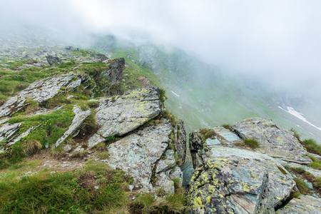 on the edge of rocky cliff of Fagaras ridge. mysterious scenery of Romanian highlands in thick fog. beautiful summer landscape. popular travel destination. couple of tourists in the distance Stock Photo