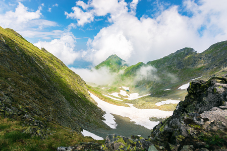 on the edge of rocky cliff of Fagaras valley. gorgeous landscape of Romanian mountains in rising clouds. popular travel destination. beautiful summer scenery with snow on the bottom of the valley Stock Photo