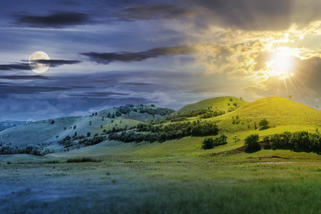 day and night time change concept above three hills in summer landscape. beautiful countryside scenery with sun and moon.  tilt-shift and motion blur effect applied. Stock Photo