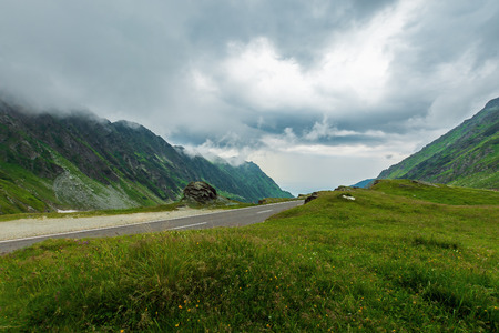 transfagarasan road in stormy weather. popular travel destination of romania. grassy meadow along on the edge of a hill. view in to the distant valley. overcast sky Stock Photo