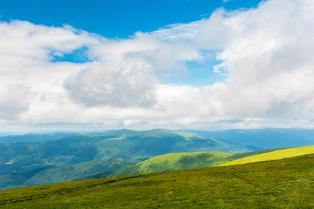 landscape in mountains. hills and meadows. sunny weather with beautiful cloudscape. grassy green slope and distant ridge. Stock Photo
