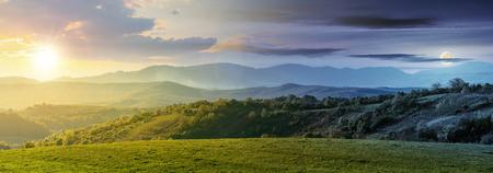 le jour et la nuit changent au-dessus du panorama de la campagne roumaine. magnifique paysage printanier dans les montagnes avec soleil et lune. terrain herbeux et collines vallonnées. paysage rural