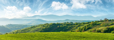 panorama of beautiful countryside of romania. sunny afternoon. wonderful springtime landscape in mountains. grassy field and rolling hills. rural scenery Stok Fotoğraf - 116824749