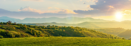 panorama of romania countryside at sunset in evening light. wonderful springtime landscape in mountains. grassy field and rolling hills. rural scenery Stock Photo