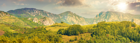 gorgeous panorama of countryside at sunset in evening light. beautiful landscape of romania. rural area on the near hills. distant ridge with rocks, cliffs and gorge. wonderful sunny afternoon Stock Photo