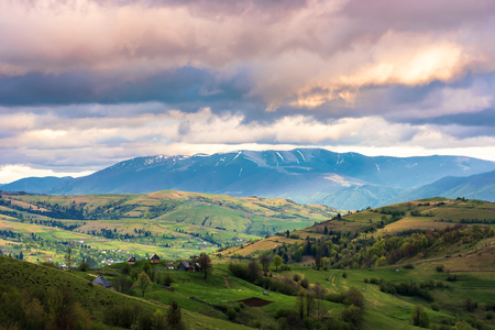 springtime countryside in mountain. grassy rural fields on hills. village in the valley. distant ridge with snowy tops. dramatic afternoon weather. cloudy sky Stock Photo