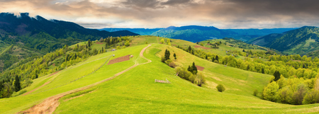panorama of a beautiful countryside in mountains. path down the grassy rural hills rolling in to the distance. ridge beneath an overcast sky in springtime