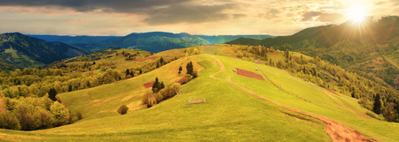 panorama of a countryside in mountains at sunset in evening light. path down the grassy rural hills rolling in to the distance. ridge beneath an overcast sky in spring