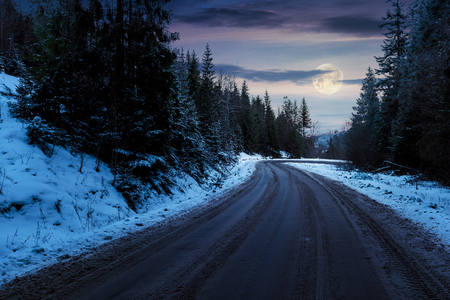 road through pine forest in mountains at night in full moon light. mysterious transportation winter scenery. path winding down the hill Stock Photo