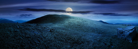 panorama with rock on the grassy hill in mountains. beautiful summer landscape in full moon light. amazing nature scenery. dramatic cloudy sky at night Stock Photo