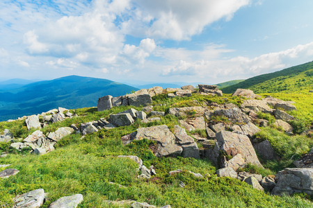 rocks on a grassy meadow in mountain. beautiful summer landscape. sunny weather with fluffy clouds Stock Photo