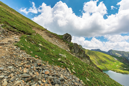 summer time in romanian carpathians. beautiful landscape of fagaras mountains. lake capra down in the valley. fluffy clouds above the ridge. rocky cliff on the hillside