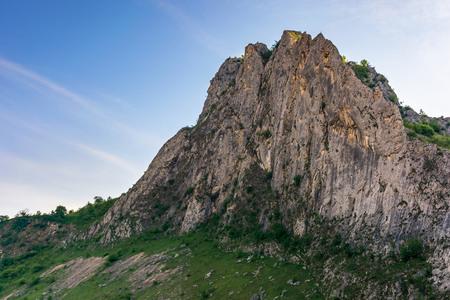 beautiful nature of romania mountains. springtime landscape at sunrise. cliff in shade beneath a blue sky