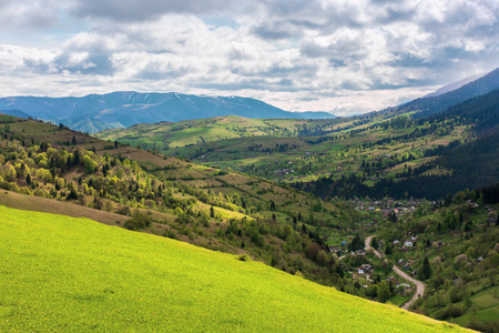 mountainous countryside in springtime. village in the valley, rural fields on hills. distant mountain ridge with spots of snow. sunny weather with cloudy sky. view from the grassy meadow