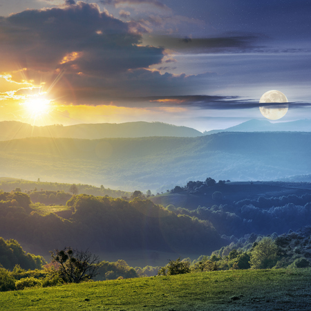 day and night time change concept above romania countryside with green rolling hills beneath a moon and sun. agricultural grassy field. mountain ridge in the distance. cloudy sky. Stock Photo
